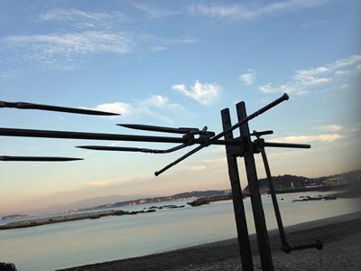 明け方の海岸に豚の丸焼き台を設置